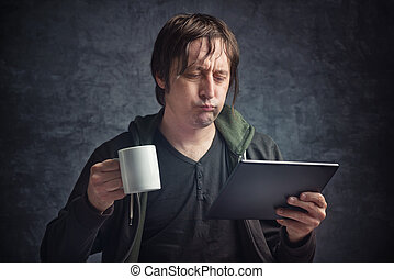 Man Reading Bad News on Digital Tablet Computer - Adult...