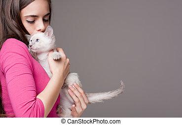 Brunette beauty with cute kitten. - Portrait of a beautiful...