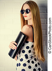 clutch bag - Fashionable lady near white brick wall. Beauty,...