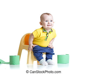 smiling child sitting on chamber pot with toilet paper rolls