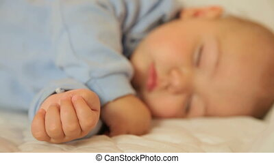 Cute baby boy sleeping on the bed in the living room