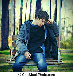 Sad Young Man - Toned Photo of Sad Young Man on the Bench in...