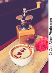 Love message on coffee cup on wooden background with vintage...