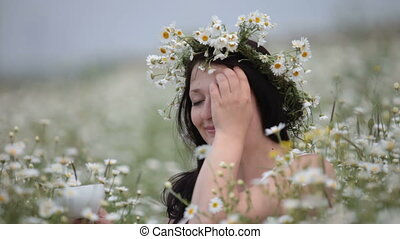 young woman drinking from a cup sitting among the daisies on...