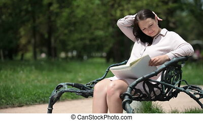 Pregnant young woman sitting on a park bench reading a book in the summer