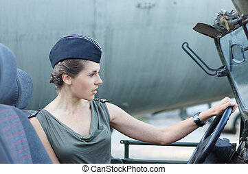 Young attractive female soldier driving the car