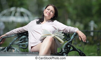 Young pregnant woman relaxing on a bench in city park...