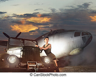 Young attractive female soldier with the plane and car