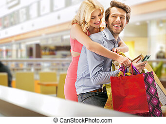 Young cheerful couple in the shopping mall - Young cheerful...