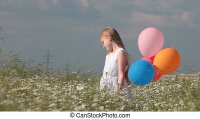 little blonde girl with colorful balloons in lush summer field