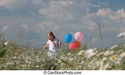 Little girl with balloons walking through flowering summer field