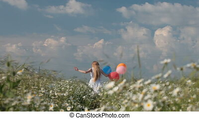 little girl with balloons runs away through the blooming summer field