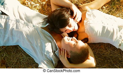 Young couple lying on the grass under a tree in autumn shot...