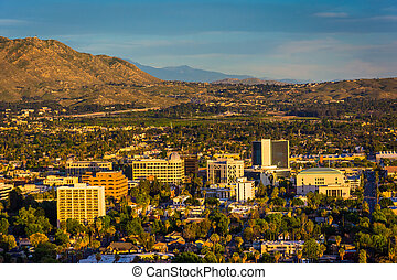 Evening light on on distant mountains and the city of...