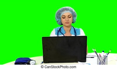 Doctor working at the computer on green screen Alpha channel...