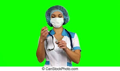 Healthcare and medicine: nurse using a syringe on green...