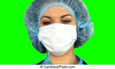 Young nurse in mask with syringe on green screen.