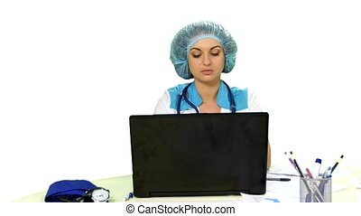Smiling doctor sitting at the computer on white background