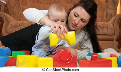 Mother with baby boy playing colored blocks on floor in the...