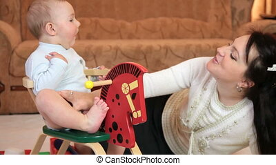 Young mother playing with her baby boy on the wooden rocking horse at home