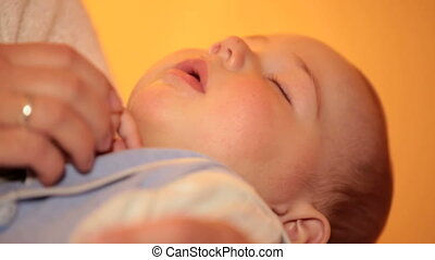 Mother holding sleeping baby boy at home close up