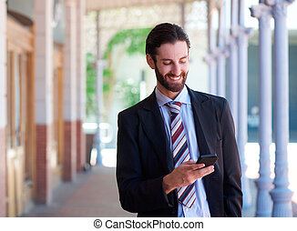 Friendly businessman smiling with mobile phone