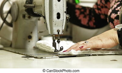 Professional tailor using sewing machine in workshop