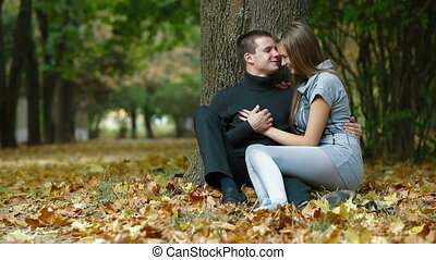 Romantic teenage couple sitting under a tree on fallen leaves in autumn park