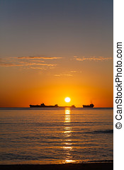 Tanker ship at sunset - Side view of silhouetted tanker ship...