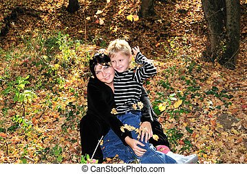leaf shedding - mother and son have a fun in the forest...