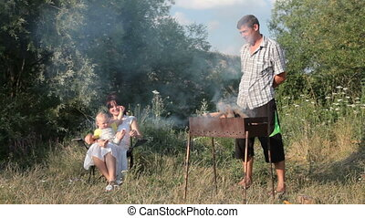 young family with child cooking shashlik on picnic in summer