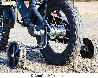Bicycle with supporting wheels stuck in loose gravel