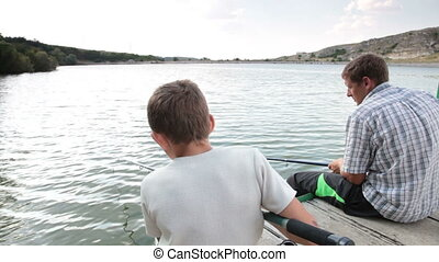 Man and boy spending weekend with fishing rod on the lake in summer