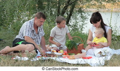 Young family with children spending weekend at picnic on the nature