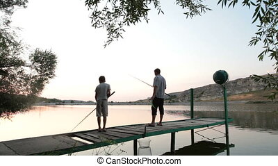 Father and son fishing on the lake shore at dusk in the...