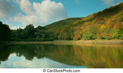 autumn landscape with a lake in the woods among the hills...