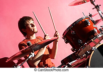 man playing on drum on red background