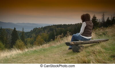 Woman is relaxing on bench, mountain landscape
