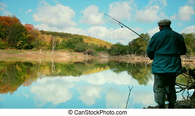 man with  fishing rod fishing on the lake in the autumn forest