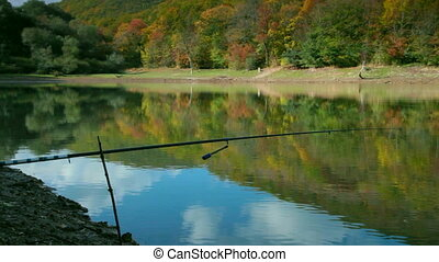 lake shore with a fishing rod in the autumn forest...