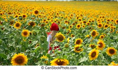 little girl walks through a field of sunflowers