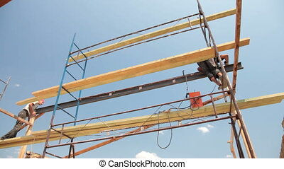 Construction workers on scaffold doing welding work