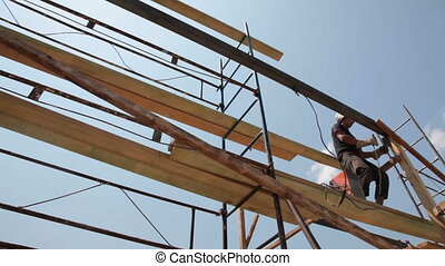 Construction worker welder doing welding work on scaffold