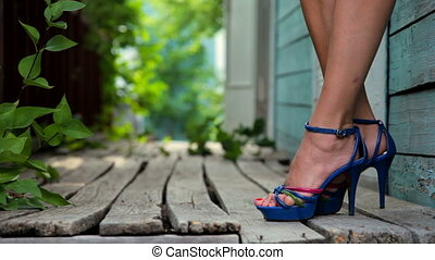 Female legs in high heels in front of an old wooden house...