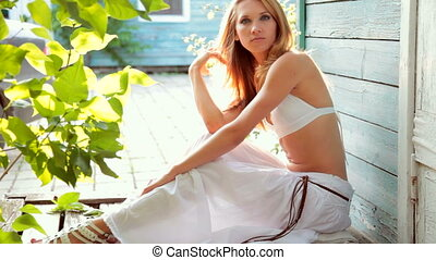 young woman sitting on an old wooden porch in sunny summer...