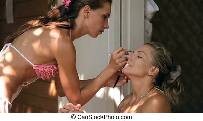 Two young women in swimsuits on the bungalow porch doing makeup in summer