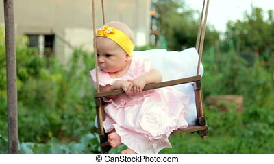 Baby girl on a swing in the backyard