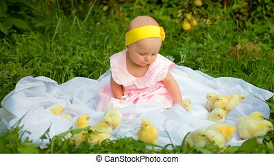 Baby girl with chicks in the garden