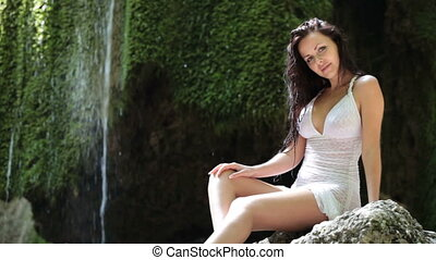 Young woman resting at a mountain waterfall in the summer woods