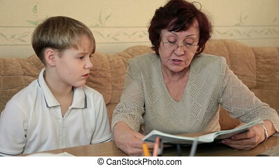 Grandmother with her grandson doing homework sitting at a...